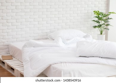 Messed bed with white pillow and blanket with natural light in the morning,Messy bed after wake up,Messy bed Concept