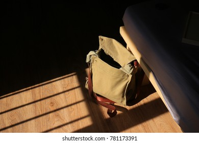 messenger bag lay on the floor in hard sunlight