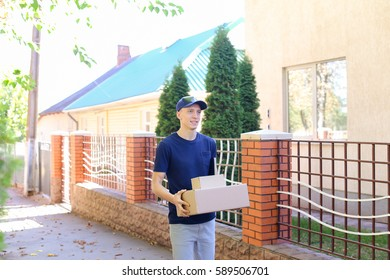 Messenger Carring Two Boxes in Hands Smiling on Background of Trees Along Street. Courier Company Provides Its Services in All Areas Ofterrain, Man of European Appearance in Uniform Carries Two Boxes