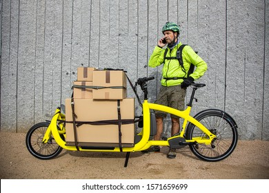 messenger with his cargo bike, looking at the route on his smart phone and talking on the phone
