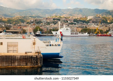 Messina, Italy landscape skyline. Travel photo. Sea port at Strait of Messina. Ionian sea, white boats, ship, and mountain range on the Italian island Sicily, Mediterranean. Blue water and cloud sky