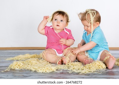 Messy baby toddlers having fun eating pasta