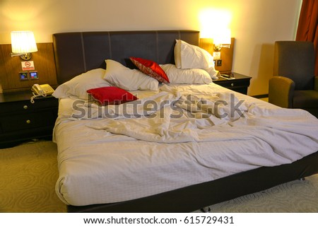 Messy Bed In The Morning Of A Hotel Room
