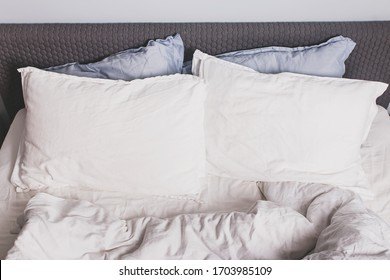 Messy bed with two pillows close-up, white bed linen.