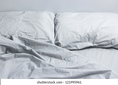 Messy bed with two pillows, gray bed linen.