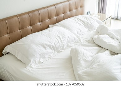 Messy bed with white pillow and blanket on bed unmade