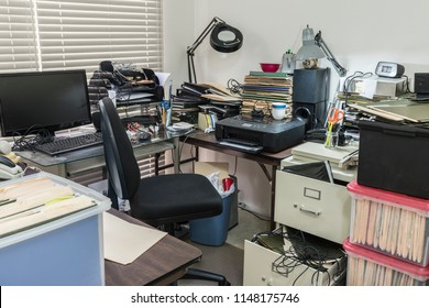 Messy business office desk with boxes of files and disorganized clutter.