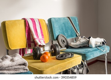 Messy and chaotic room of a teenager. Could be gym interior or on campus. Towels, bag and sport shoes on colorful chairs.