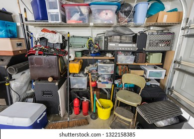 Messy cluttered garage shelves with vintage electronics, housewares and sports equipment.
