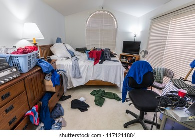 Messy, cluttered teenage boy's bedroom with piles of clothes, music and sports equipment.