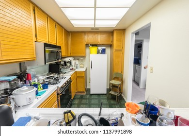 Messy condo kitchen with oak cabinets, tile countertops, gas stove, green flooring and piles of dishes.