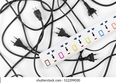 Messy of electrical cords plugs and wires unconnected electrical power strip or extension block  with messy wires, top view on white background, messy electric equipment flat lay concept.