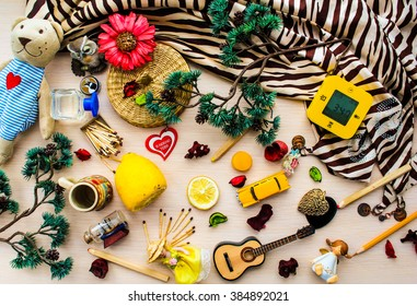 Messy flat lay of yellow things with green branches of pine tree on fair wooden background, tiger scarf. Flowers, petals, lemon, toy bear, some dolls and another toys and alarm clock. Top view.