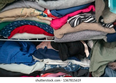Messy folded clothes crammed in a closet on a shelf. Depicting woman's wardrobe, consumerism, cleaning up, tyding up, purging, etc.