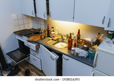 Messy kitchen after party. Beer bottles, plates in a sink, wine bottle