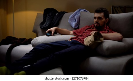 Messy man lying on sofa, watching tv, covered with chips crisps, untidiness