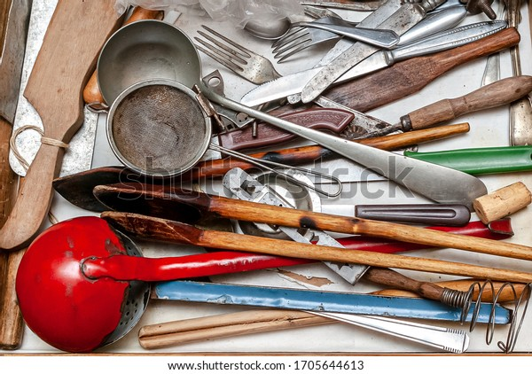 Messy miscellaneous kitchen utensils. Diverse used vintage metallic and wood tools.