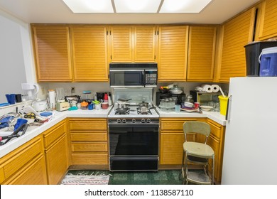 Messy old condo kitchen with oak cabinets, tile countertops, gas stove, green flooring and piles of dishes.