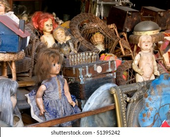 Messy packed room full of antique objects like dolls, an accordion, wicker or basket chairs
