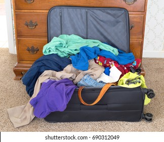 Messy Packed Suitcase of a man's on vacation in a rental house or hotel.  It's a horizontal closeup of clean and dirty clothes mixed and piled high and falling out onto the side and floor area.