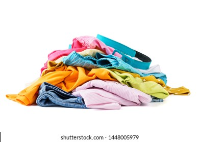 Messy pile of colorful summer clothes isolated on white background.
