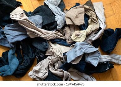 Messy pile of old worn out textile socks in a clutter. Concept of decluttering clothes.