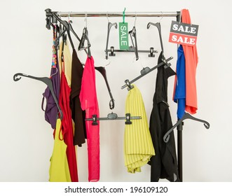 Messy rack of clothes and hangers after a big sale. Sale sign for summer clothes on a clearance rack with colorful summer outfits and accessories.