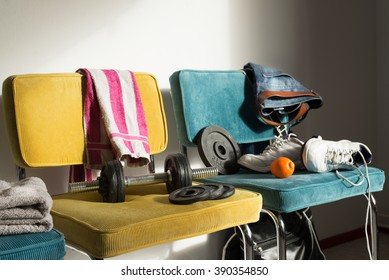 Messy room of a boy or teenager being active. Chaotic gym or fitness interior. Chairs with jeans, towels, sneakers and dumbbells.