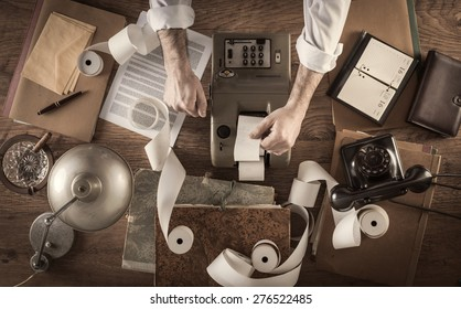 Messy vintage accountant's desktop with adding machine and paper rolls, he is working with the calculator
