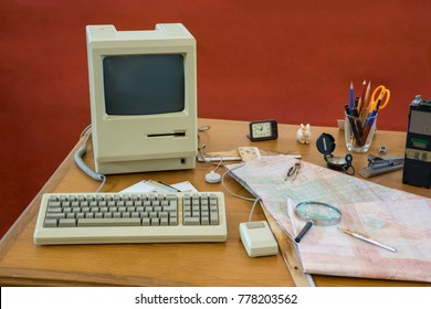 Messy vintage desk with obsolete computer, map, magnifying glass, communication radio and compass
