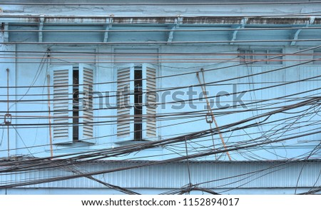 Messy wires attached to the electric pole, the chaos of cables and wires on an electric pole in Bangkok with old light blue building and windows in back ground , Bangkok Thailand,