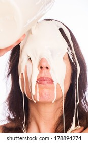 Messy woman with milk on her face.