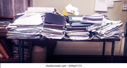 Messy workplace with stack of old papers