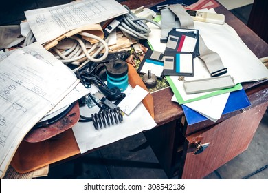 Messy workplace with stack of paper on table