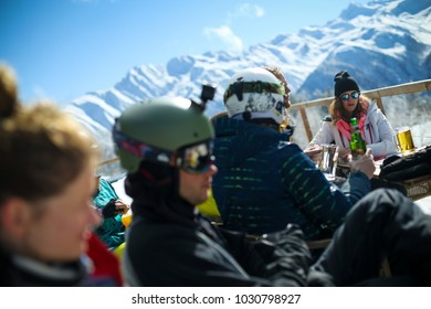 Mestia, Svaneti, Georgia - February 8, 2018: Group of young male and female snowboarders and skiers sitting in the mountain top cafe in ski resort in Mestia, Svaneti (Svanetia) region of Georgia.