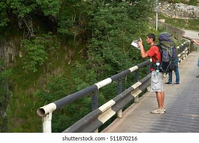 MESTIA/GEORGIA - JUNE 20, 2016: Hiker with big backpack photographing from the bridge in Mestia town, Svaneti, Georgia