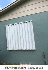Metal accordion storm shutters closed to protect a home from the oncoming hurricane.