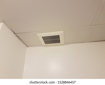 metal air vent or register on the ceiling with white walls