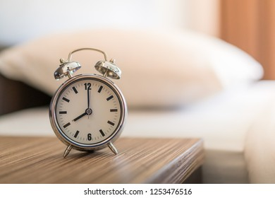 Metal Alarm clock on white bed 8 am.