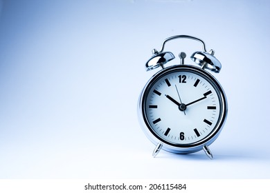 Metal Alarm clock work time on white background 10 am.