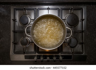Metal aluminum pan on traditional iron stove cooker boiling water with chicken stock for cooking pasta
