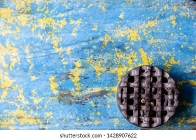 Metal ash tray (ash pan, ash pit) lying on a shabby old table. The texture of the table is amazing. Blue and yellow paint color. Free space for text. Wallpapers for your desktop.