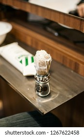 Metal barber's brush with shaving cream sitting on a wooden table