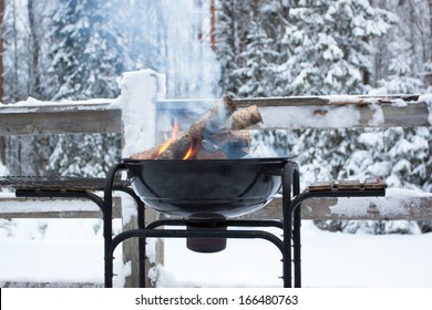 metal basket with a glowing wood. Camp fire at a cold winter day in forest