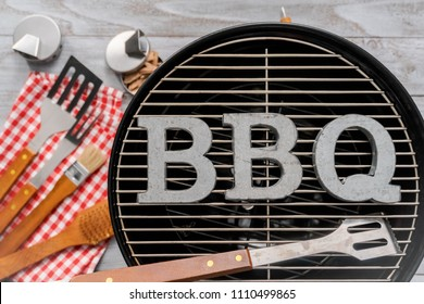 Metal BBQ sign with BBQ cooking tools on a wood background.