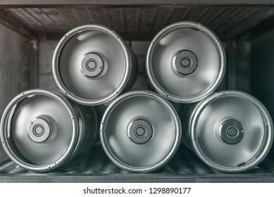 Metal beer kegs lie in a row on the shelf