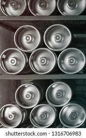 Metal beer kegs lie in a row on the shelf. Vertical frame