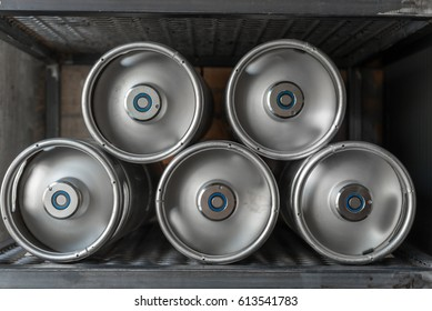 Metal beer kegs lie in a row on the shelf