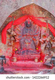 Metal bells offered by devotees at Kali Temple. Shrine full of vermillion red pigment powder to worship Goddess Kali at Dhulikhel in Nepal