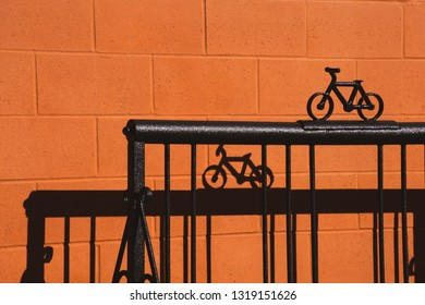 A metal bike rack against a terra cotta painted block wall creates an interesting linear work of abstract art using shadows and light.